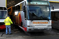 Man washing a coach with a jet sprayer, Wales
