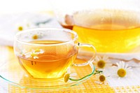 Teacup and teapot with herbal soothing camomile tea