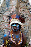 Vertical waist shot of tribal warrior with horizontal blue, red and white paint across cheeks and nose and down cheeks to chin with large graffiti pai...