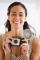Mixed race woman holding old_fashioned camera