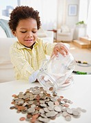 Black boy emptying jar of coins on table