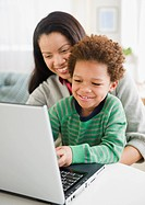 Mixed race mother using laptop with son