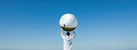 Holding aloft globe displaying image of single tree