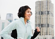 Hispanic woman running in city