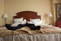 Chinese businessman sleeping in hotel bed