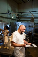 Mixed race bakery owner writing on clipboard