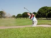 Man playing golf, stuck in bunker