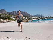 Young man jogging on beach