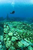 scuba diver between walls of the underwater mills, Lago di Capo d´Acqua, Abruzzo, Italy