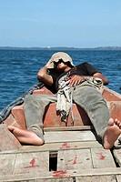 Man sleeping in boat, Cambodia