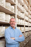 Portrait of smiling cheese maker in cellar with aged farmhouse cheddar cheese wheels