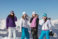 Four teenage girls in ski clothes using their mobile phones
