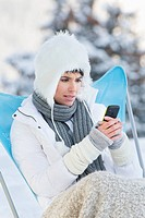 Young woman using mobile phone in snow