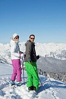 Young couple of skiers looking back