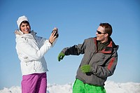 Young woman in ski wear taking a photo of her boyfriend