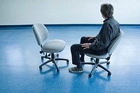 Man sitting on a chair in an empty office