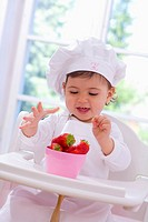 Little girl in chef´s hat eating strawberries