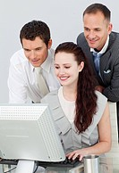 Three business people using a computer in the office