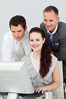 Smiling businesswoman and two businessmen using a computer in the office