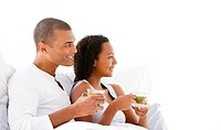 Cheerful couple drinking a cup of tea lying on their bed at home