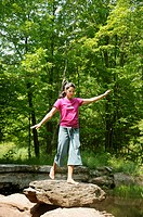 Woman balancing on a rock, low angle view