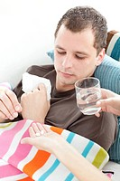 Sick man taking medicine on the sofa at home