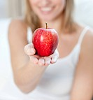 Close_up of a blond woman showing an apple at home