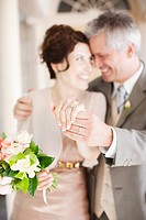 Mature bride and groom displaying rings