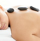 Sleeping woman lying on a massage table having a stone therapy