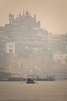 A boat is rowed on a typically foggy morning in the Ganga Ganges River at Varanasi, Uttar Pradesh, India, Asia