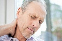 Close_up of a man rubbing his neck