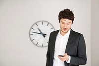 Businessman standing in front of a clock and using a mobile phone