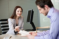 Female real estate agent showing a brochure to a man