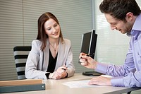 Man signing documents with a female real estate agent sitting in front of him