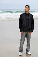man standing on beach wearing a coat and smiling
