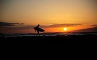 Hawaii, Oahu, Waikiki, Silhouette of a surfer walking on a rock wall at sunset