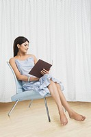 Woman reading a book and sitting on a chair