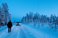 Van car crossing Taiga forest, Kuhmo, Finland, near the Russian border in February