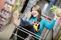 Portrait of a young woman sitting in shopping cart and holding a pineapple