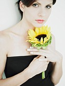 Portrait of a young woman holding a sunflower