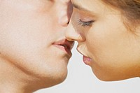 Close_up of a mid adult man and a young woman kissing