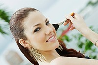 Portrait of a young woman applying make_up with a make_up brush