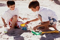 Two boys playing with sand pail and shovel on the beach