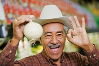 Portrait of a senior man holding a white onion and making an ok sign