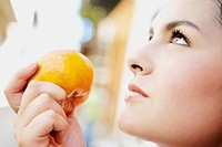 Close_up of a young woman holding an orange