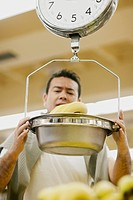 Low angle view of a mid adult man holding a weighing scale