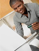 Mid adult man holding a credit card in front of a laptop