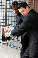 Portrait of two businessmen holding handles on a door