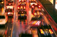Blurred image of a traffic jam with cars seen from behind with their red lights and reflections on the wet street after a heavy rain at night, Central...
