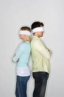 Blindfolded couple standing back to back